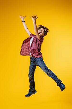 Un retrato de cuerpo entero de un joven brillante saltando en el estudio sobre el fondo amarillo. Niños, moda.