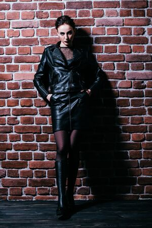 A full length portrait of a beautiful woman wearing a black leather jacket. Fashion, style.
