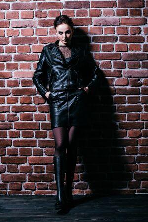 Un portrait en pied d'une belle femme portant une veste en cuir noire. Style de mode.