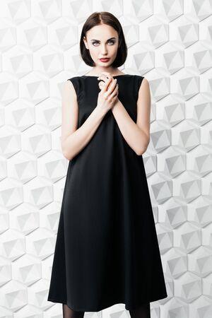 A portrait of a beautiful woman wearing a black dress. Fashion, style. Stock Photo