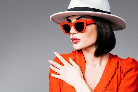 A portrait of a beautiful woman wearing a hat and sunglasses. Fashion, style, beauty, optics.