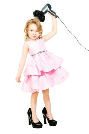A full length portrait of a pretty girl in a pink dress and high-heeled shoes posing in the studio over the white background with a hairdryer. Kids, fashion, beauty. Banco de Imagens
