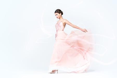 A full length portrait of a charming lady in a wedding dress posing in the studio. Wedding fashion, bride. Фото со стока