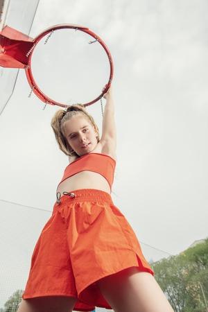 Un portrait d'une adolescente sportive posant sur la pincée de basket-ball. Mode sportive, mode de vie actif, basket-ball.
