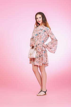 Un ritratto a figura intera di una ragazza romantica sorridente in posa in studio sopra il backround rosa. Moda casual estiva. Archivio Fotografico