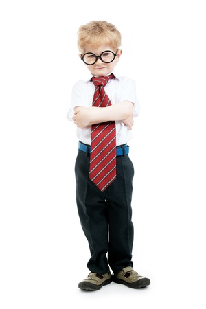 A full length portrait of a serious young schoolboy posing in the studio over the white background. Kids fashion for school, education.