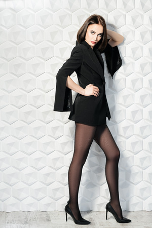 A full length portrait of a beautiful sexy woman wearing a black blazer. Fashion, style, beauty.