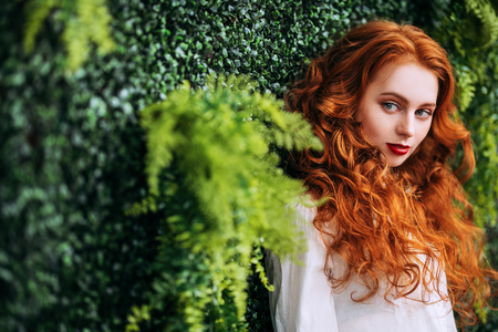 A portrait of a lovely mysterious girl on green plant background. Beauty, cosmetics.
