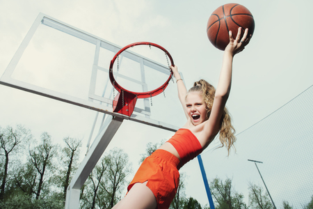 A portrait of a sporty teenager girl posing on the basketball pinch. Sport fashion, active lifestyle, basketball.
