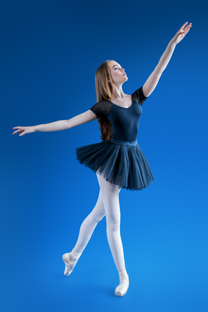 A full length portrait of an elegant refined ballet female dancer posing in the studio over the blue background. Talent, fashion for ballet dancers.