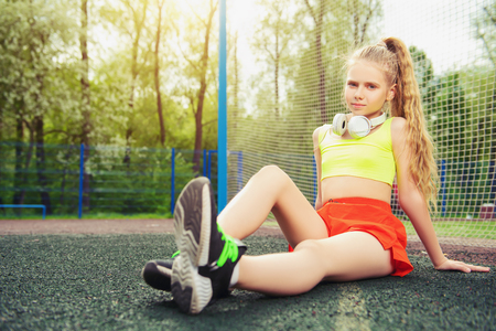 A full length portrait of a sporty teenager girl posing on the sports ground. Sport fashion, active lifestyle.