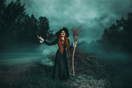 A portrait of an angry witch with a broodstick near the forest. Magic, dark force, spell. 版權商用圖片