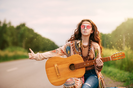 Beautiful hippie girl is standing on a highway and catching a passing car. Spirit of freedom. Fashion shot. Bohemian, bo-ho style.