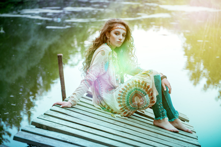 Beautiful hippie girl is sitting on the platform in the background of lake outdoor. Contemporary bohemian style. Spirit of freedom. Fashion shot. Bohemian, bo-ho style. Stock Photo