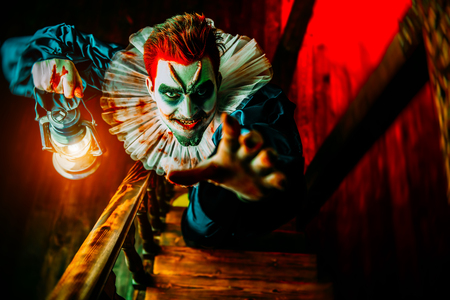 A portrait of an angry crazy clown from a horror film with a lantern on the stairs. Halloween, carnival. Stock Photo - 126759185