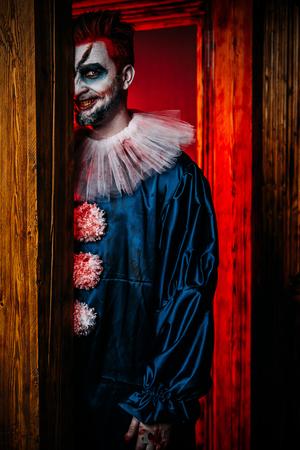 Portret wściekłego klauna z horroru chowającego się za drzwiami. Halloween, karnawał. Zdjęcie Seryjne