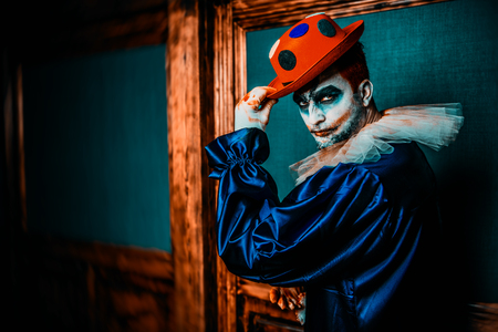 A portrait of an angry crazy clown from a horror film with a hat. Halloween, carnival.