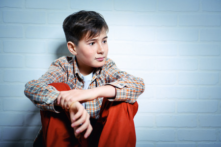A portrait of an emotional young boy in casual clothes. Fashion for male teenagers.