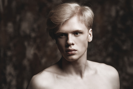 Portrait of a shirtless young man with blond hair posing at studio over grunge background. Men's beauty and health. Archivio Fotografico - 126759300