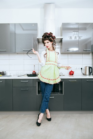Beautiful young housewife stands wearingin home clothes and apron on kitchen background. Pin-up style. Fashion home shot. Full length portrait.