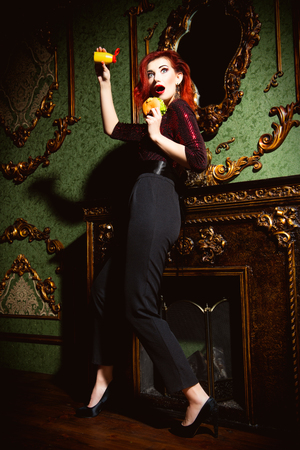 Un ritratto a figura intera di una bella donna in posa all'interno vintage e con un hamburger con salsa. Bellezza, moda, interni.