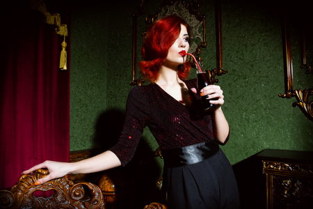 A portrait of a beautiful woman posing in the vintage interior and having a drink. Beauty, fashion, interior. Stok Fotoğraf