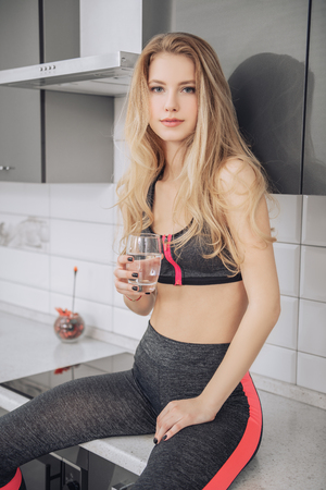 Portrait of a beautiful girl in jogging suit with a glass of water at the kitchen in home. Fitness at home. Beauty, fashion.