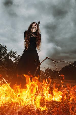 Ein Porträt einer wütenden Hexe, die zur Verbrennung gefesselt ist. Magie, dunkle Kraft, Zauber.