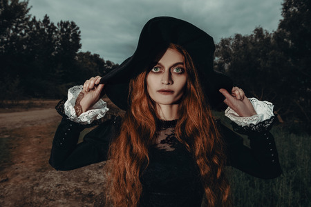 A portrait of an angry witch near the forest. Magic, dark force, spell.