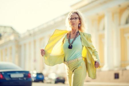 A portrait of an elderly stylish woman walking in the street. Beauty, city fashion.