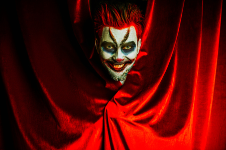 A portrait of an angry crazy clown from a horror film behind the red curtain. Halloween, carnival. Stock fotó