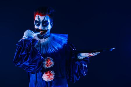 Un portrait d'un clown fou en colère d'un film d'horreur avec un plateau. Halloween, carnaval. Banque d'images