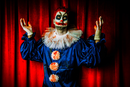 A portrait of an angry crazy clown from a horror film over the red curtain. Halloween, carnival. Reklamní fotografie