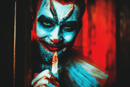 A close up portrait of an angry clown from a horror film hiding behind a door. Halloween, carnival. Фото со стока