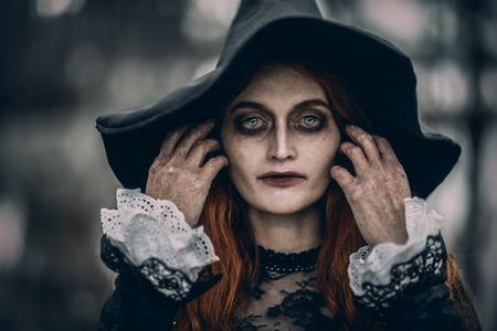 Un retrato de cerca de una bruja aterradora pelirroja. Magia, fuerza oscura, hechizo.