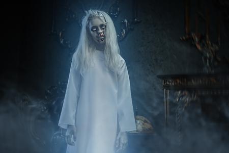 Ein Porträt eines beängstigend blassen Mädchens aus einem Horrorfilm im Vintage-Interieur. Zombie, halloween. Standard-Bild