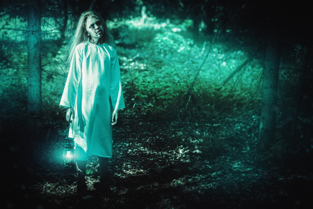 A full length portrait of a scary pale girl from a horror film in the forest with a lantern. Zombie, halloween.