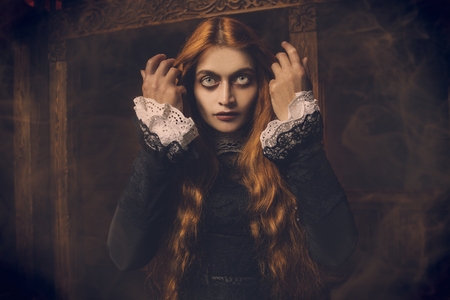 Un retrato de una bruja aterradora pelirroja en su guarida. Magia, fuerza oscura, hechizo. Foto de archivo