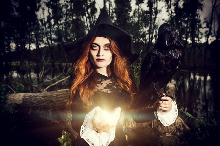 A portrait of an angry witch with a black raven outdoor. Magic, dark force, spell.