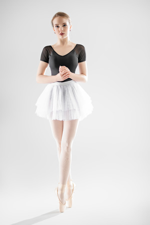 A full length portrait of an elegant refined ballet female dancer posing in the studio over the white background. Talent, fashion for ballet dancers. Stock Photo - 126948843