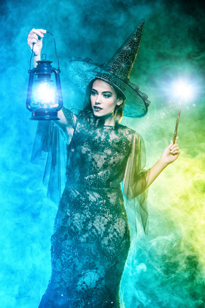 A beautiful lady in a costume of witch holding a lantern. Halloween. Celebration.