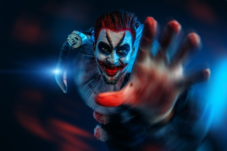 A portrait of an angry crazy clown from a horror film with a knife. Halloween, carnival. 스톡 콘텐츠