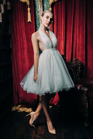 A full length portrait of an elegant refined female ballet dancer posing in the vintage interior. Talent, fashion for ballet dancers. Stock Photo