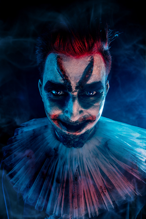 A close up portrait of an angry clown from a horror film. Halloween, carnival.