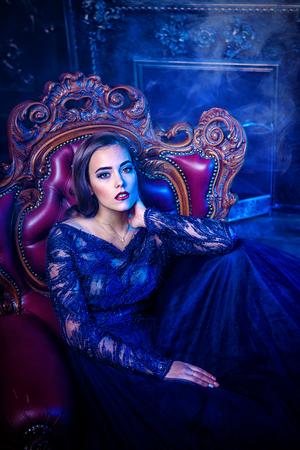 Una dama encantadora está sentada en un sillón en un interior clásico. Belleza. Moda. Foto de archivo