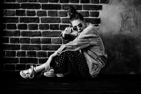Un retrato monocromático de cuerpo entero de una elegante chica de moda brillante posando interior sobre la pared de ladrillo. Moda casual de verano.