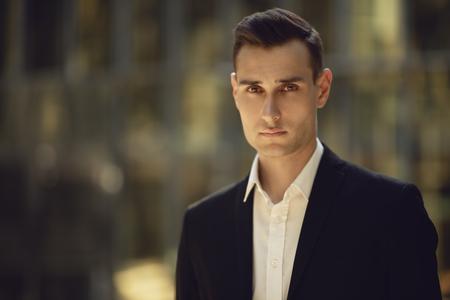 Ein Porträt eines gutaussehenden jungen Mannes, der auf der Straße aufwirft. Männer Schönheit, Mode.
