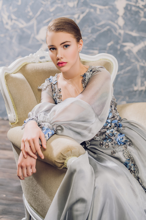 A portrait of a charming lady in a silver dress posing on the chair. Fairy tale, fashion. 写真素材 - 127048176