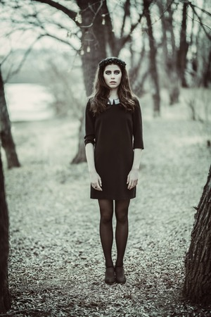 A full length portrait of a beautiful mysterious girl in black walking in the forest. Beauty, fashion, nature. 스톡 콘텐츠