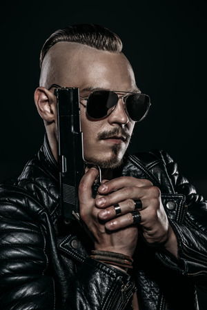 Dark portrait of a serious gangster man with  gun wearing black leather jacket. Stock Photo